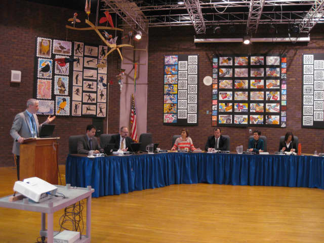 Superintendent Jere Hochman presents the latest look at the 2013-14 budget in Wednesday night's school board meeting, which more than 60 employees, parents and students attended.