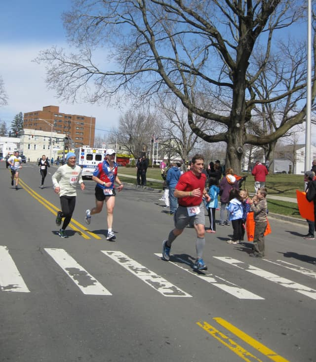 A crowd of runners approaches the finish line in the Danbury Half Marathon.