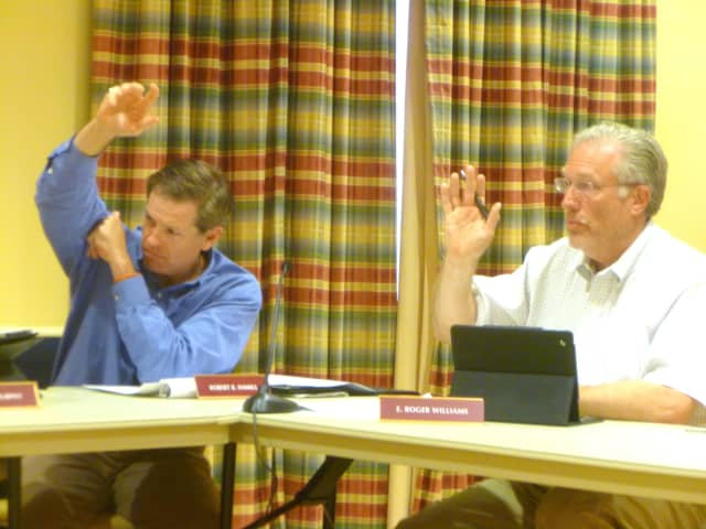 Town Council members Robert Hamill (left) and E. Roger Williams vote in favor of New Canaan's spending plan.