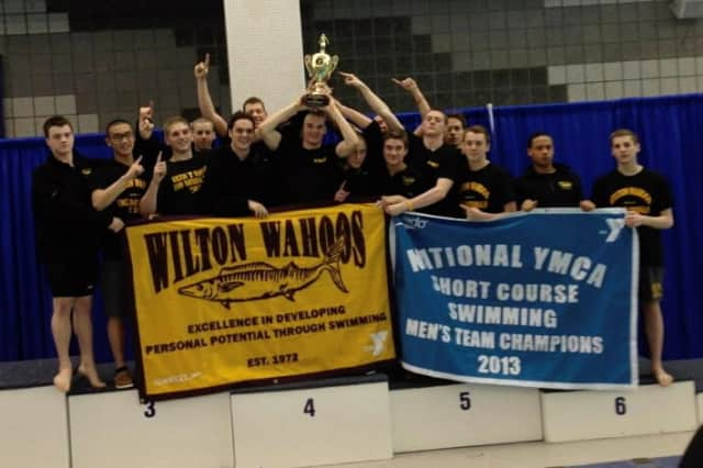 The Wilton Wahoos boys team holds its national championship banner after winning the YMCA Short Course title last weekend in North Carolina.