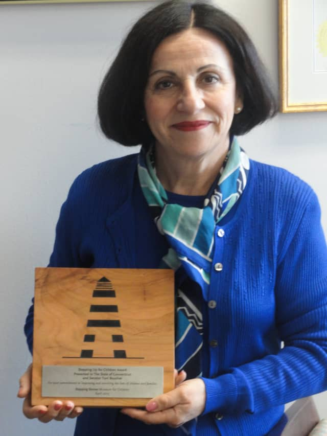 """State Sen. Toni Boucher of Wilton shows off the """"Stepping Up for Children"""" award she received from the Stepping Stones Museum."""