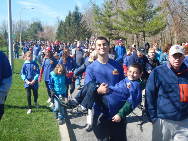 """Ossining resident and Somers senior Anthony Torchia holds his cousin Nicholas Ruvo during the """"Go the Distance Walk"""" to benefit the Maria Fareri Children's Hospital."""