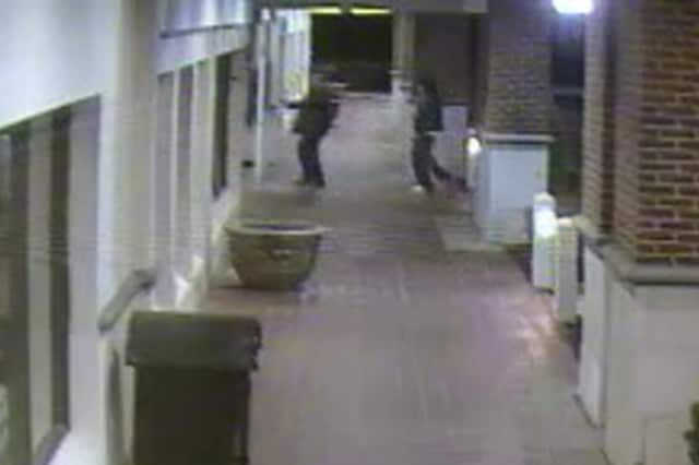 This photo shows one of the suspects forcing an employee to open Fairfield's Lenox Jewelers in a robbery in April 2013.