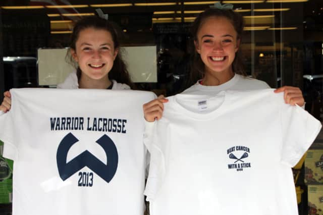 Wilton High School girls lacrosse players Charlotte Noels and Maeve Kennard show off T-shirts that will be for sale during Tuesday's benefit game for the National Foundation for Cancer Research.