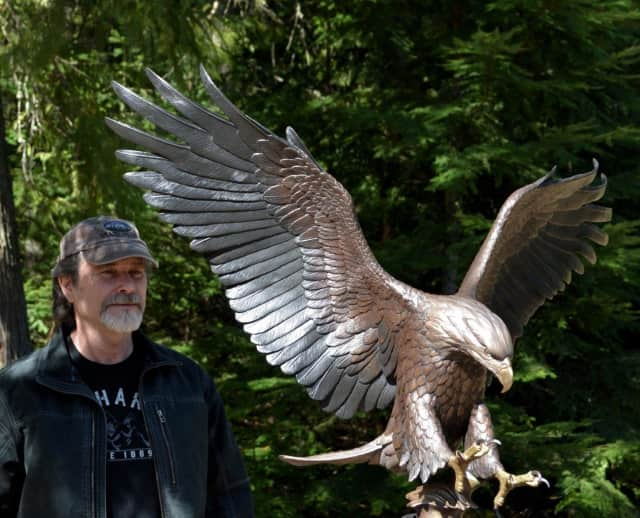 """Idaho sculptor and Army veteran Mike Curtis stands with the """"Tribute Eagle"""" he created for Somers' Lasdon Park in honor of all Westchester veterans."""