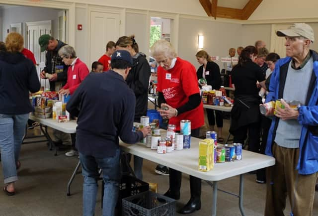 """Nearly 100 volunteers helped to sort through the bags of food that was donated for the postal service food drive, """"Stamp Out Hunger."""" The National Association of Letter Carriers' 24th annual """"Stamp Out Hunger"""" food drive is Saturday in Greenwich."""