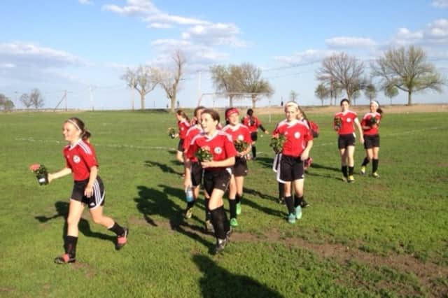 Girls on the New Canaan Red U12 girls soccer team carry flowers to their mothers after Sunday's win over Bridgeport.