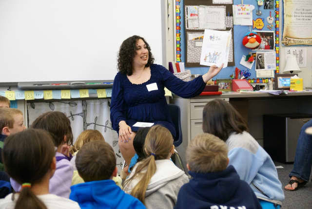 Marybeth Gioffre Nisco, chairwoman of the Wilton Education Foundation's Read Aloud Day, reads to children at Cider Mill School Monday.