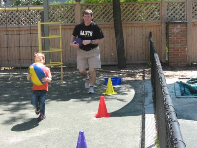 A father and son play, and exercise, together at Bright Horizons Wilton recently. Center organizers say one way to keep kids active and healthy this summer is to make exercise fun.