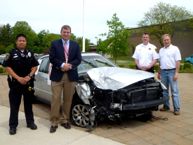 (From Left): School Resource Officer Jason Kim, Principal Bryan Luizzi, Capt. Leon Krolikowski, and Anthony Ceraso, owner of AC Auto Body, outside New Canaan High School with a damaged car reminding students not to drink and drive.
