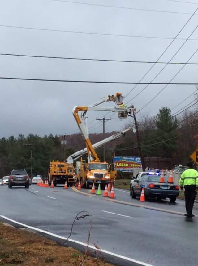Utility crews repair a pole after a crash Wednesday morning on South Main Street in Newtown.