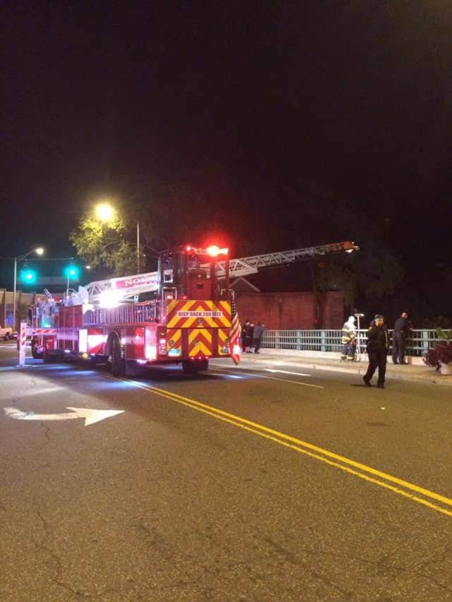 Emergency crews search early Friday from a bridge in Norwalk for a man missing in the Norwalk River.