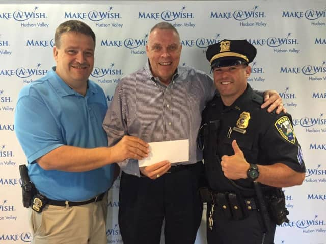 """Ossining PBA President Sgt. Aaron Zimmerman and Det. Pete Carpenter presented Make-A-Wish Hudson Valley with a check for $1250, monies raised from the """"Dunk a Cop"""" booth at Saturday's Ossining Village Fair."""