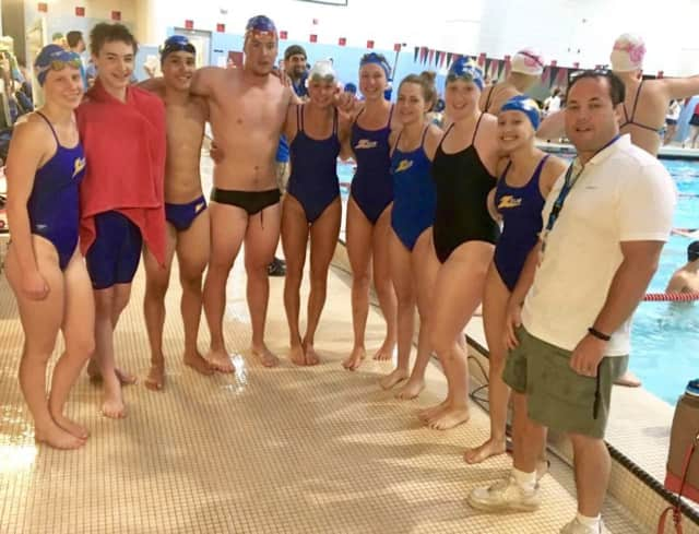 Omar Cruz, right, stands with swimmers from the ZEUS team in Norwalk at one of his final meets. Cruz stepped down after 14 years with the team to devote more time to his real estate business.