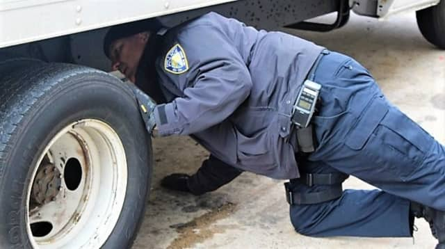 PAPD CVI Francis Franco inspecting a commercial vehicle.