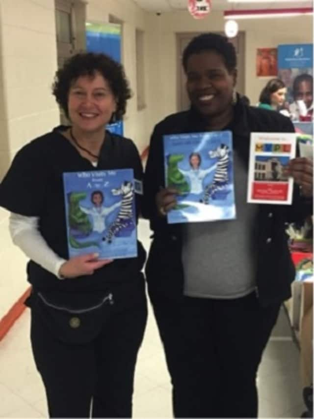 "Author Joanne Roos, left, and school librarian Denise Mincin, hold copies of ""Who Visits Me From A to Z,"" at a recent session of Parent University at the Grimes Elementary School in Mount Vernon. The books were given away free to participants."