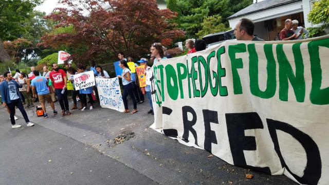 Demonstrators rally Thursday against hedge fund greed across from the Indian Harbor Yacht Club in Greenwich.