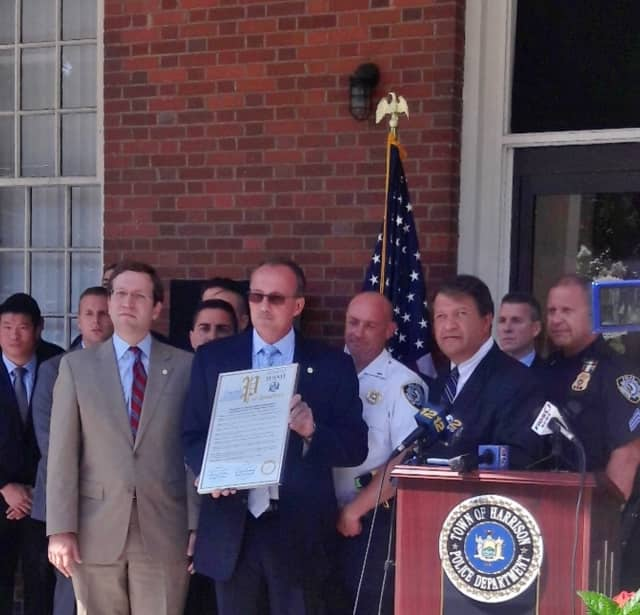 Harrison Police Chief Anthony Marraccini, holding proclamation, flanked by Assemblyman David Buchwald, left, and State Sen. George Latimer, right.