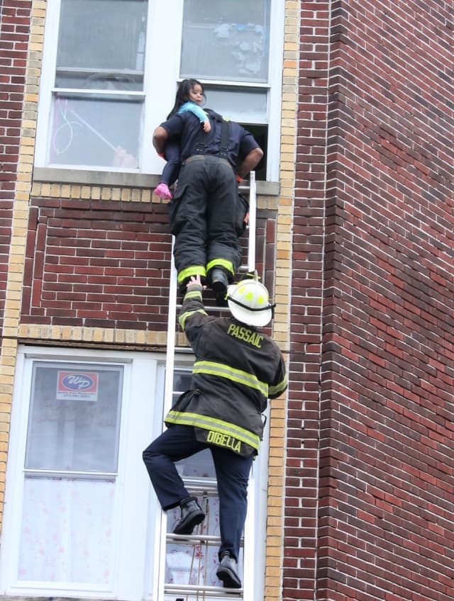 City firefighter Ricardo Figueroa climbed a ground ladder and carried the child down with help from Deputy Chief Chris DiBella.