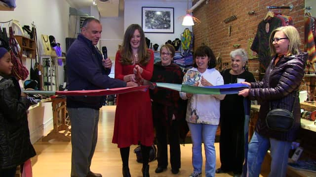 Jeorjia Shea, center, in red, cuts the ribbon at the official opening of her artisan boutique, Quirkshop, in Peekskil. At left is Peekskill Mayor Frank Catalina.