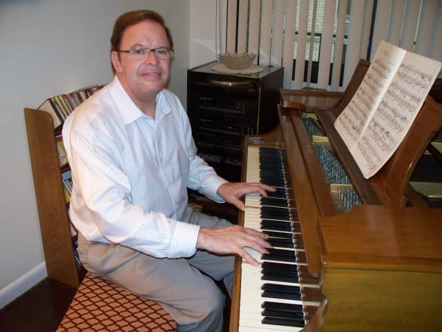 Randy Wine sits in front of his circa 1908 handmade Steinway piano in his Hackensack condominium.