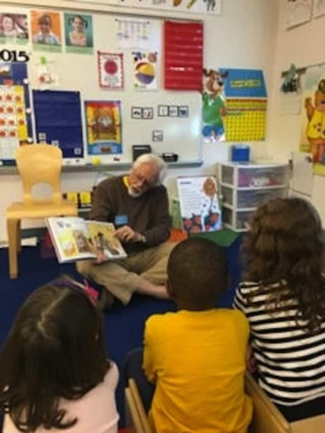 Daily Voice Community adviser Roy Fuchs reads to a class at Trumbull Early Childhood Education Center.