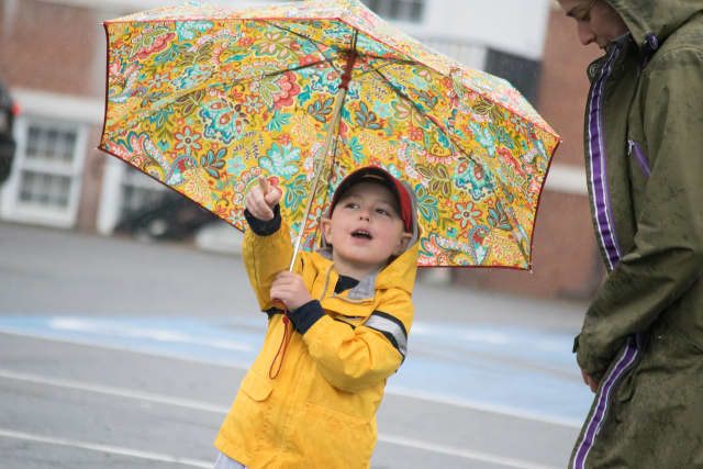 A child keeps dry under an umbrella during Sunday's Run Like A Mother 5k race in Ridgefield.