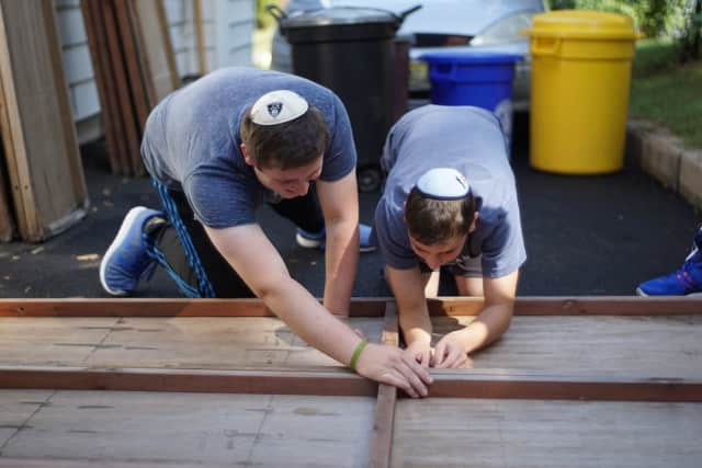 Safely@Home volunteers help a senior veteran erect his sukkah for the upcoming Sukkot festival.