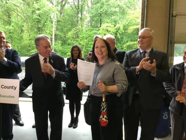 Rockland County Executive Ed Day gives a signed copy of his Executive Order to ROSA Volunteer Deborah Munitz.