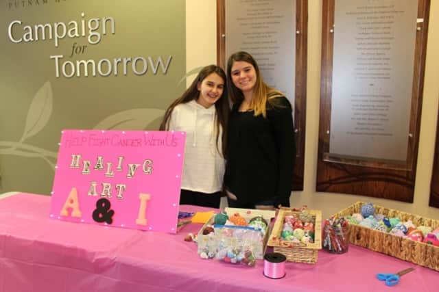 Adelina Ademaj, on left, and Isabella DeChico sell holiday ornaments and pens in the Putnam Hospital Center lobby.