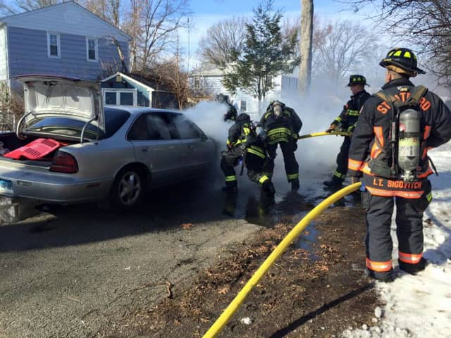 Firefighters in Stratford tackle a car fire.
