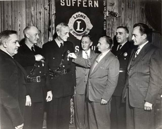 Members of the Suffern Lions Club award medals to Suffern police officers in this vintage 1950s photograph.