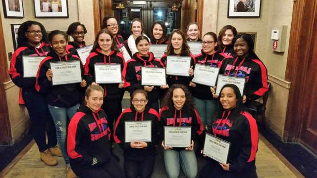Peekskill's Girls Varsity Swim Team holding their Scholar Athlete certificates.