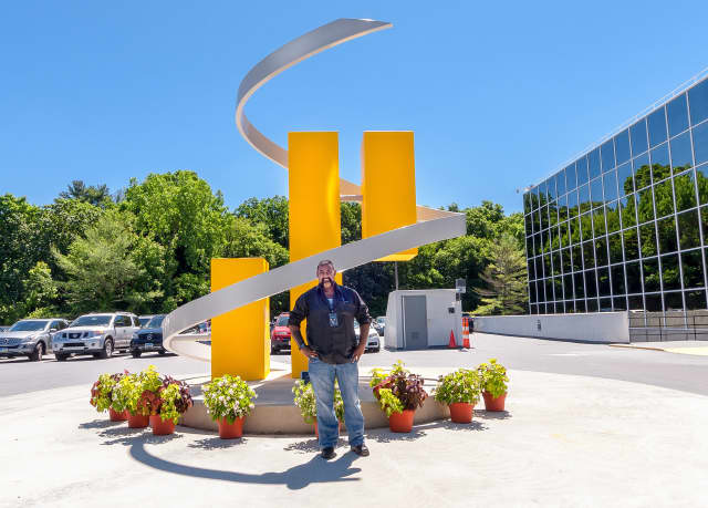 William Seepaul Jr. stands in front of a sculpture he created at Synchrony Financial in Stamford.