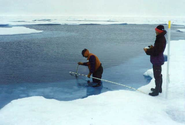 Researchers collect data in a melted ice pack of the Arctic Ocean while studying Arctic melt and other aspects of climate change.