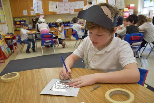 Tinsmithing was one activity Main Street School fourth-graders enjoyed during the annual Colonial Day celebration.