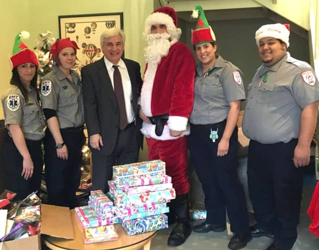 """""""Elves"""" Leanne Censullo, Jennifer Banks, Ivette Triana and Jose Rios with """"Santa"""" (Eric Crafton) and Anthony D'Urso, chief supervisor of psychology at the Audrey Hepburn Children's House"""