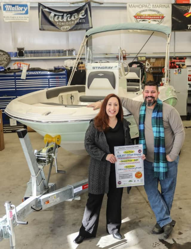 Faith Ann Butcher, Chairwoman of The Greater Mahopac-Carmel Chamber of Commerce, with Charles Melchner Jr. of Mahopac Marine in front of the 2017 19-foot Stingray that will be the grand prize in the Chamber Scholarship Raffle.