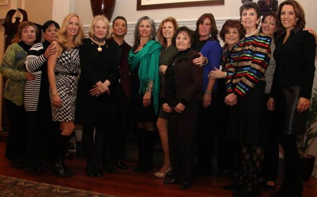 The staff of Bayside Travel is shown at travel show last year. The company has moved from Larchmont to Bronxville.