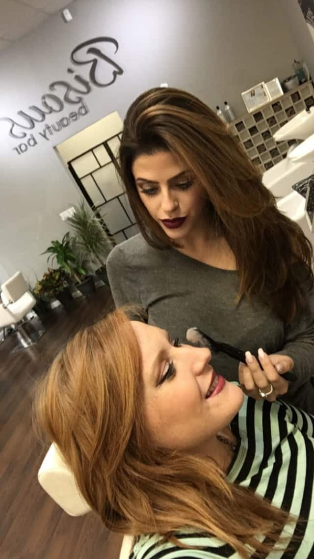 Whitney Diacono applies makeup to a client. Her salon does makeup, blowouts and lashes.