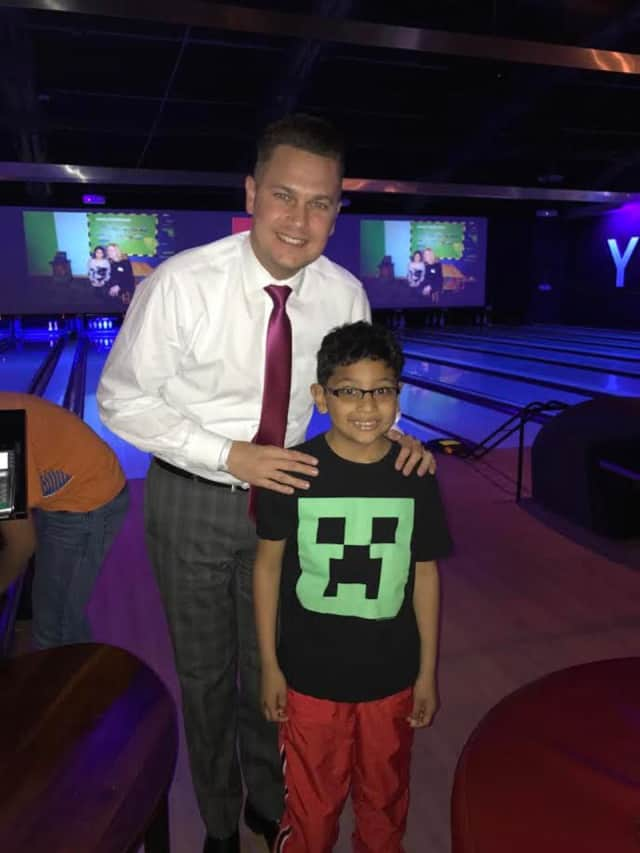Brandon Oldham of Norwalk, mentor in the program, with his mentee, Ulysses, enjoy bowling.