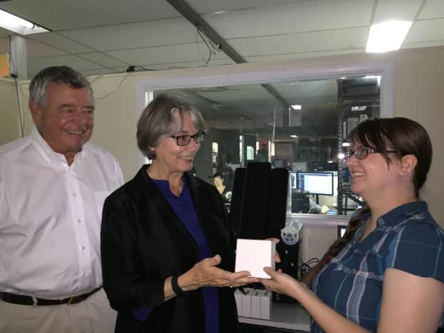 Bob Riggs, Co-Chair of the Eastchester 350th Anniversary committee, and Eloise L. Morgan,  Bronxville Village Historian, deliver the first of 114 microfilm reels of old local weekly newspapers to an employee (right) of Hudson Archival.