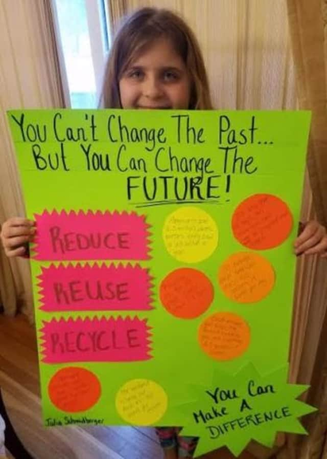 Julia Schmidberger, a fourth grader at Somers Intermediate School, with her Earth Day poster.