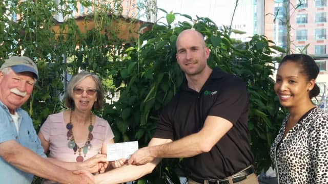 Ann-Marie Mitroff, receiving a check for $10,000 from Matt Shue, the Domino plant's refinery manager.