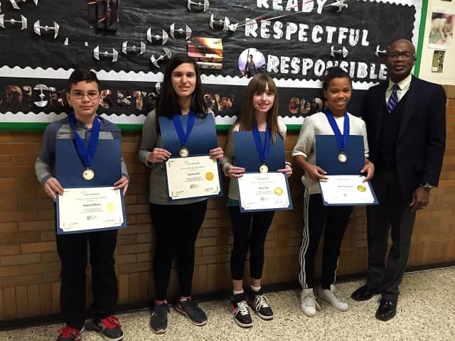 Each of the four members from Isaac E. Young Middle School's investment team recieved a certificate and medal honoring their first-place finish in the Stock Market Game.