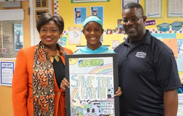 Olivia Moxey (center), whose 2016 Earth Day poster won the New York State Senate's 35th District Earth Day poster contest, is joined by her father (right) and state Sen. Andrea Stewart-Cousins (left).