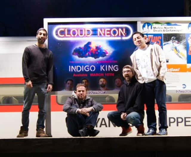 Indigo King poses in front of their billboard at the Ossining Train Station