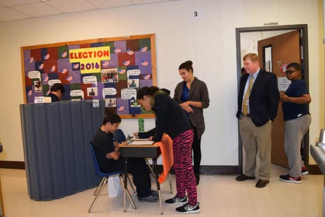A student votes behind the privacy barrier while another signs in to vote. Teaching Assistant Ana Pascarelli and BOCES Superintendent James Ryan look on.