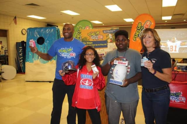 Former Giants wide receiver Amani Toomer and Lisa Porter of Porterdale Dairy Farm stand with two Peekskill City School District students.