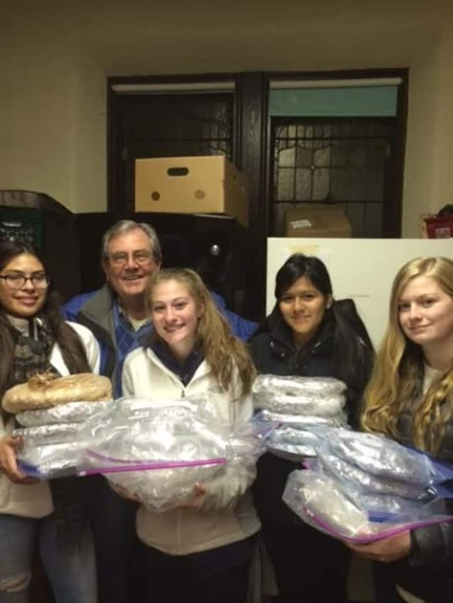 Martin Engelhardt Jr., president of the Ossining Food Pantry, accepts the donation of fresh-baked pies from local Girl Scouts Catherine Kamp, Samantha Santiago, Jessica Quizphi and Michelle Zaruma.